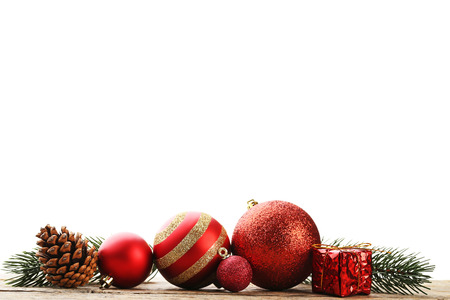 Christmas baubles with gift box and cone on wooden table 免版税图像