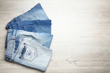 Folded jeans on wooden table