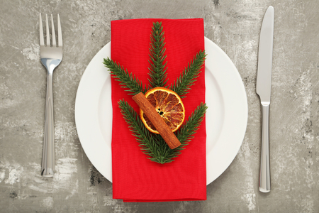 Kitchen cutlery with fir-tree branches, cinnamon and dried orange in white plate