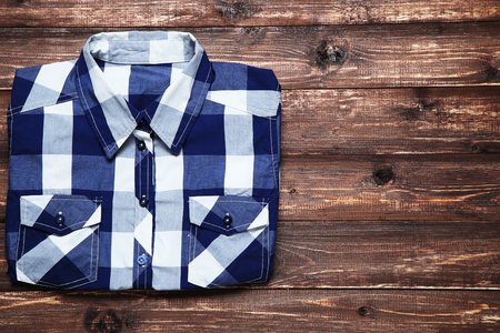 Folded shirt on brown wooden table