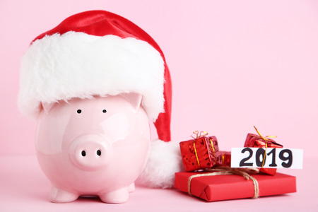 Pink piggybank in santa hat with gift boxes on pink background