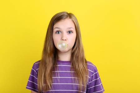 Young girl blowing bubble gum on yellow background