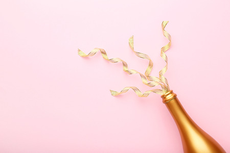 Champagne bottle with ribbons on pink background Stock fotó