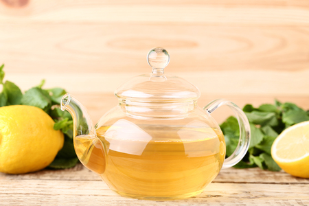 Glass teapot with mint leafs and lemons on wooden table