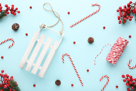 Wooden sleigh with candy canes and small baubles on blue background