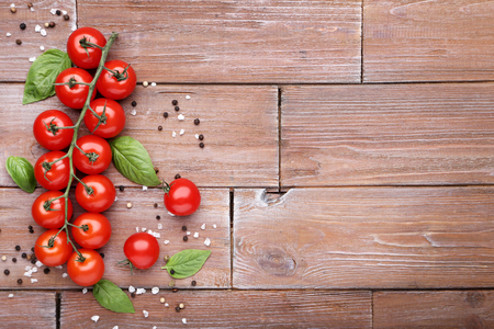 Cherry tomatoes with basil leafs and spices on brown wooden table