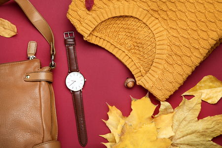 Folded sweater with leather bag, wrist watch and autumn leafs on red background 版權商用圖片