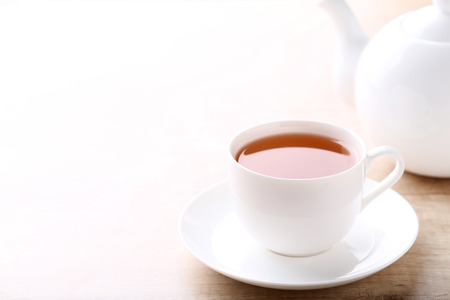 Cup of tea with teapot on wooden table