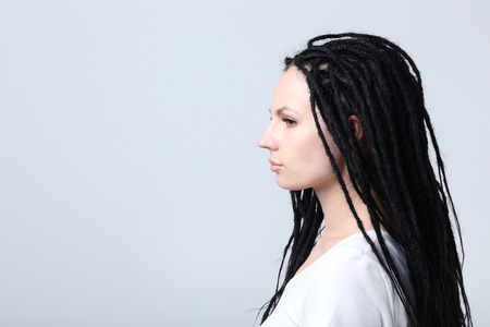 Cute young woman with dreadlocks on grey background Stock Photo