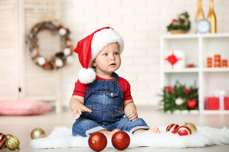 Baby boy in santa hat with baubles sitting on floor at home