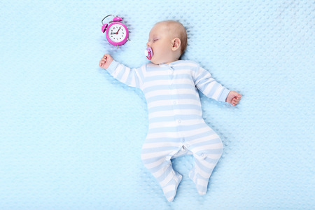 Baby boy with alarm clock sleeping in blue bed Imagens