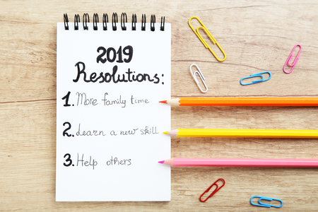 Inscription 2019 resolutions in notepad with colorful pencils and paper clips