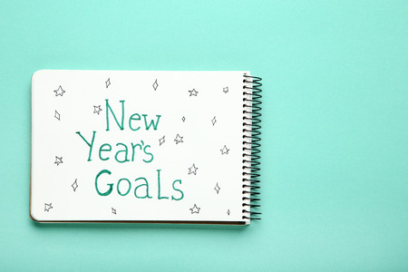 New year goals in notepad on mint background