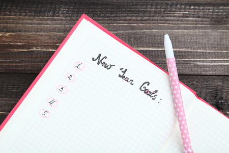 New year goals in notepad with pen on wooden table