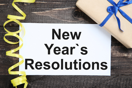 New year resolutions on sheet of paper with ribbon and gift box