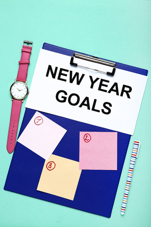 New year goals on sheet of paper with clipboard, pen and wrist watch
