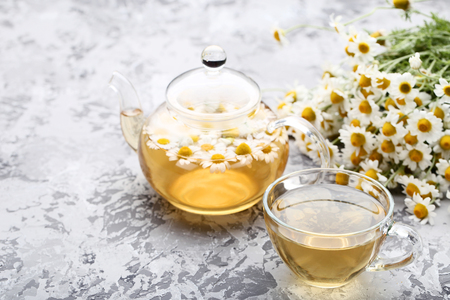 Cup of tea with chamomile flowers on grey background