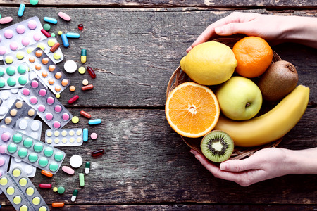 Female hands holding ripe fruits in basket and colorful pills on wooden table