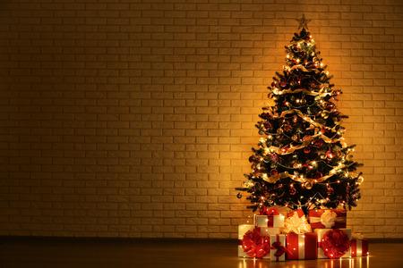 Árbol de Navidad con adornos y cajas de regalo sobre fondo de pared de ladrillo