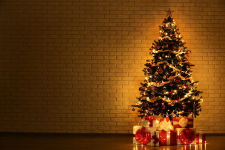 Christmas tree with decorations and gift boxes on brick wall background