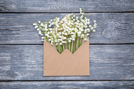 Lily of the valley flowers with envelope on grey wooden table