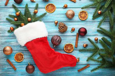 Red stocking with christmas decorations on wooden table