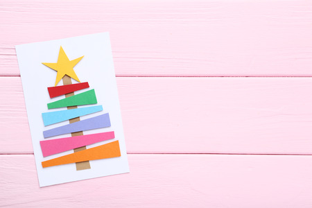 Handmade greeting card with paper fir tree on pink wooden table