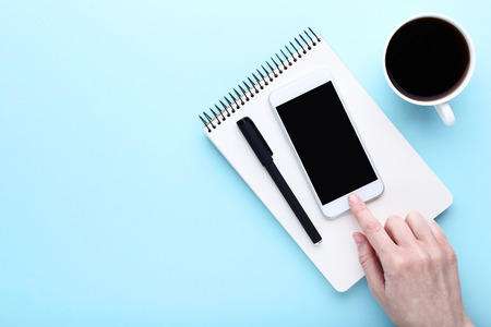 Female finger pressing smartphone button with cup of coffee and notebook on blue background