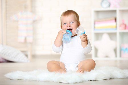 Baby boy drinking water from bottle and sitting on carpet at home Banque d'images