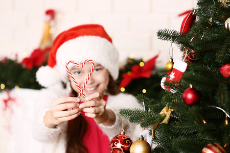 Young girl with candies near christmas tree at home