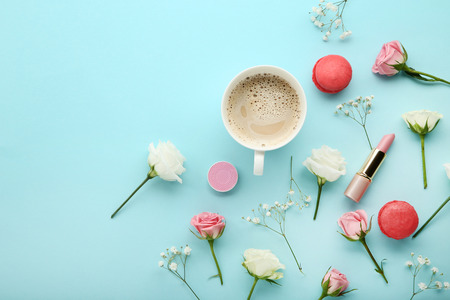 Flowers with cup of coffee and macarons on blue background