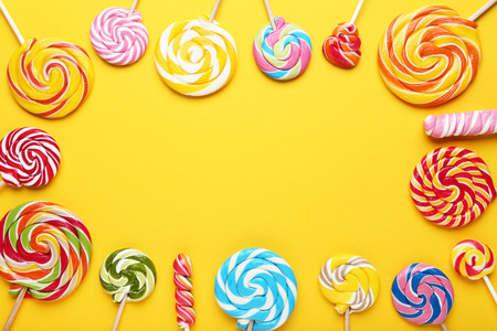 Colorful lollipops on yellow background Banque d'images