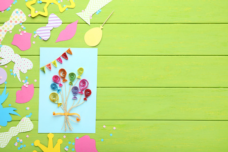 Colorful booth props for party and paper balloons on green wooden table