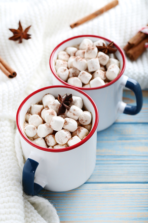Cappuccino with marshmallows in mugs and knitted scarf on wooden table