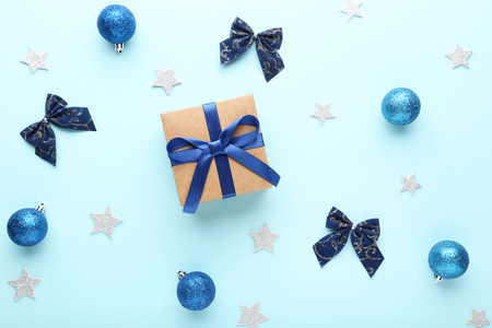 Christmas baubles with gift box and bows on blue background