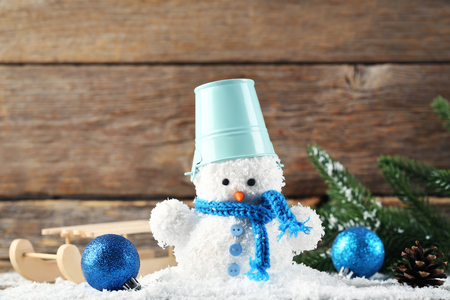 Small snowman toy with bucket, wooden sleigh and baubles