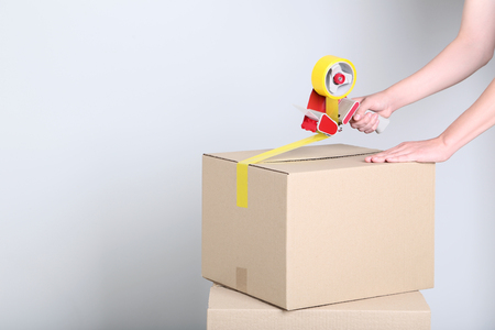 Female's hands packaging cardboard box with dispenser on grey background