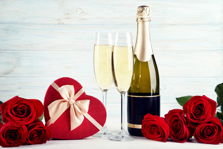 Champagne bottle with glasses, gift box and bouquet of red roses on wooden table 版權商用圖片