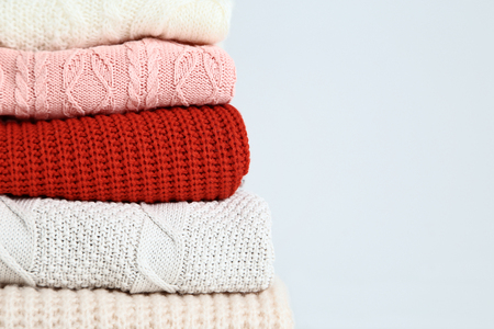 Stack of folded sweaters on grey background Archivio Fotografico