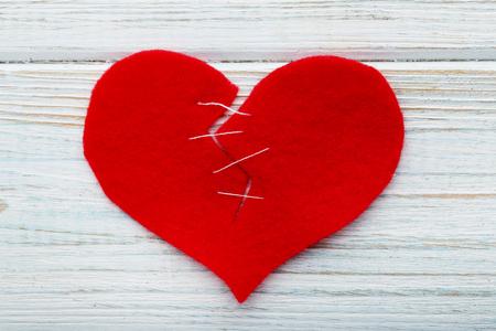Broken red heart on white wooden table