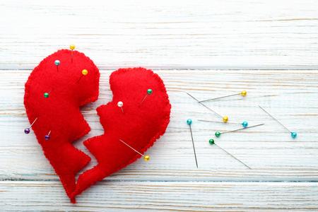 Corazón rojo roto con agujas en la mesa de madera blanca Foto de archivo