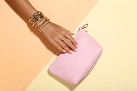 Female hand with bracelets and handbag on colorful background Фото со стока