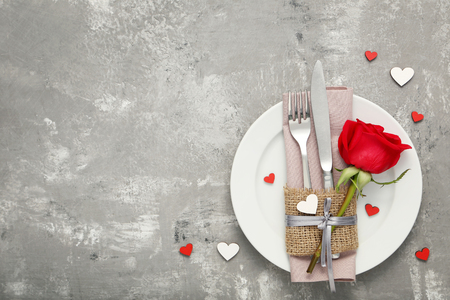 Kitchen cutlery with red rose in white plate on wooden table