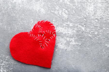 Broken red heart on grey wooden table