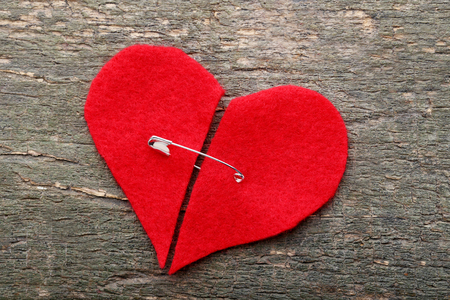 Broken red heart with pin on grey wooden table