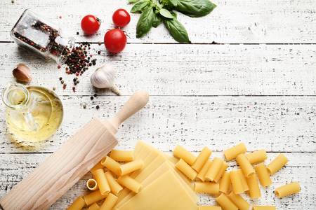 Different pasta with tomatoes, basil leafs and oil on wooden table Foto de archivo