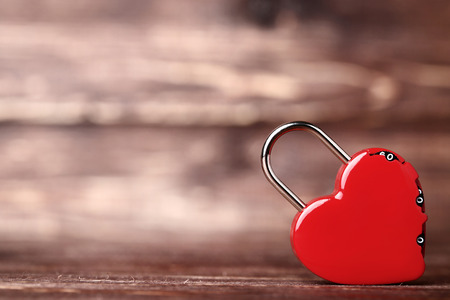 Red heart shaped padlock on brown wooden table 写真素材 - 115582530