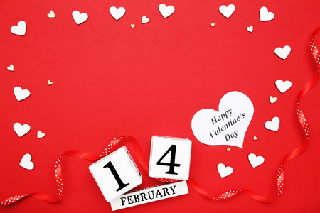 White hearts with wooden calendar and word Happy Valentine Day on red background