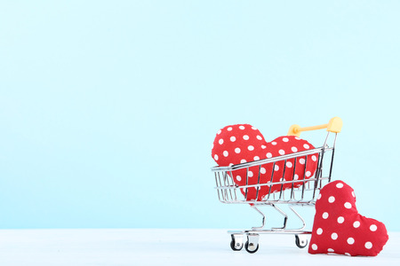 Shopping cart with red fabric hearts on blue background
