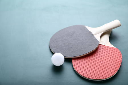 Table tennis rackets with ball on green background Banque d'images - 115584871